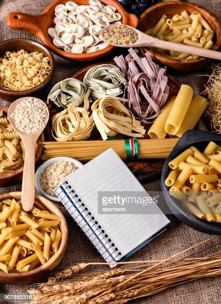 Italian pasta and recipe note pad on a wooden table in a kitchen