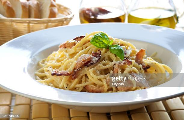 Italian pasta carbonara in a plate atop bamboo placemat