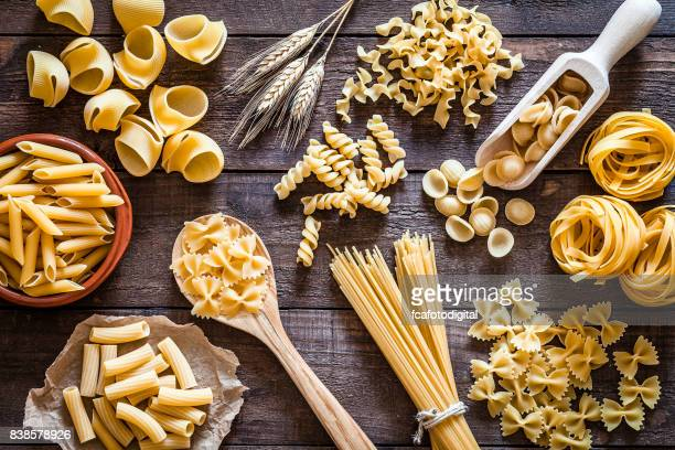 italian pasta collection on rustic wooden table - pasta stock pictures, royalty-free photos & images
