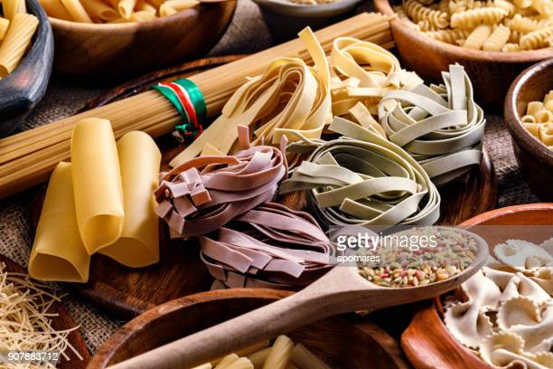 Italian pasta on rustic pots and wooden table in a kitchen