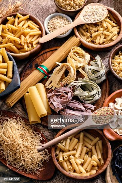 Pâtes italiennes sur pots rustiques et table en bois dans une cuisine