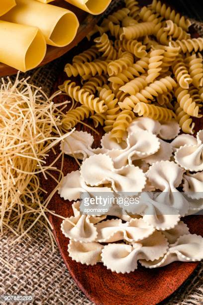 Italian pasta on rustic wooden table in a kitchen. Close-up on Faqrfalle or Bow tie pasta.