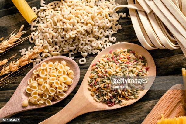 Italian pasta on rustic wooden table in a kitchen. Colored Orzo and Conchiglie pasta in a wooden spoons.