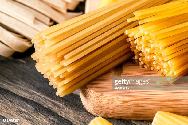 Italian pasta over rustic wooden table in a kitchen. Close-Up of Spagetti pasta.