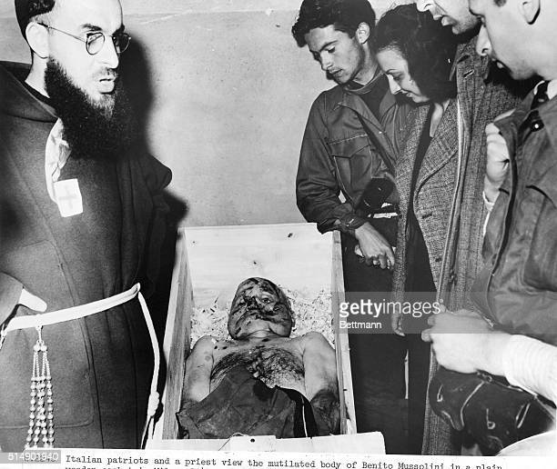 Italian patriots and a priest view the mutilated body of Benito Mussolini in a plain wooden casket in Milan 1945