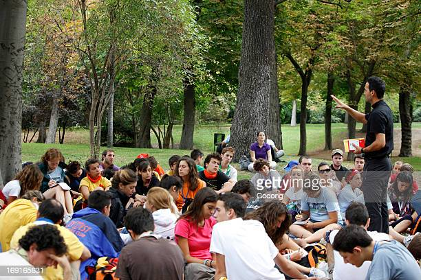 Italian pigrims listening to a priest in Retiro Park during World Youth Day