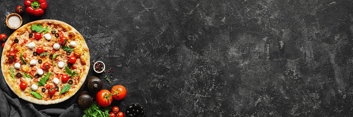 Italian pizza and pizza cooking ingredients on black concrete background 1042321668