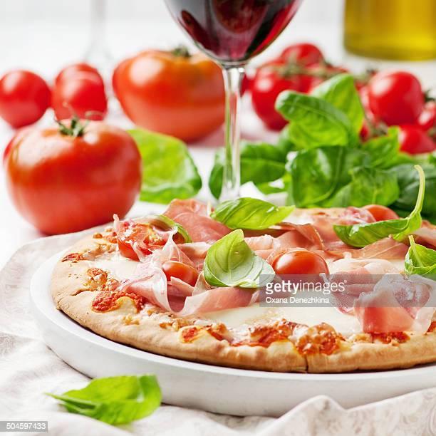 Italian pizza with mozzarella, ham and tomato