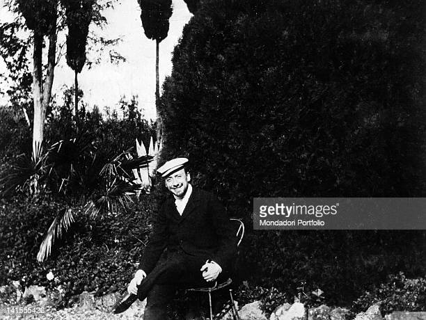 Italian poet and writer Gabriele D'Annunzio sitting in the garden of the villa La Capponcina posing for a photo by the actress Eleonora Duse...