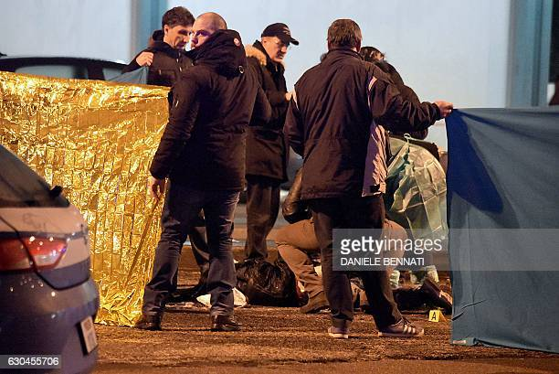 TOPSHOT Italian police and forensics experts gather around the body of suspected Berlin truck attacker Anis Amri after he was shot dead in Milan on...