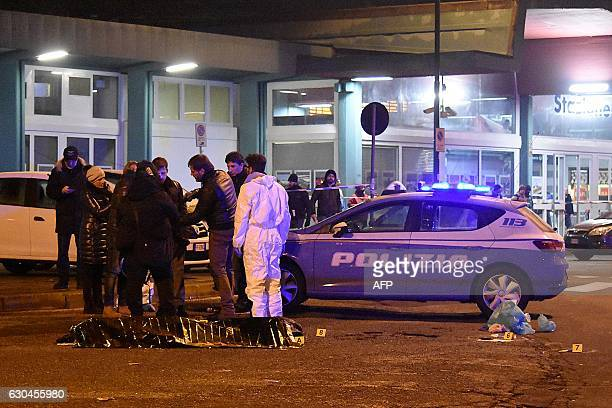 Italian police and forensics experts gather around the body of suspected Berlin truck attacker Anis Amri after he was shot dead in Milan on December...