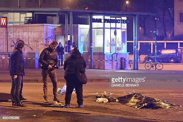 TOPSHOT Italian police and forensics experts stand by the body of suspected Berlin truck attacker Anis Amri after he was shot dead in Milan on...