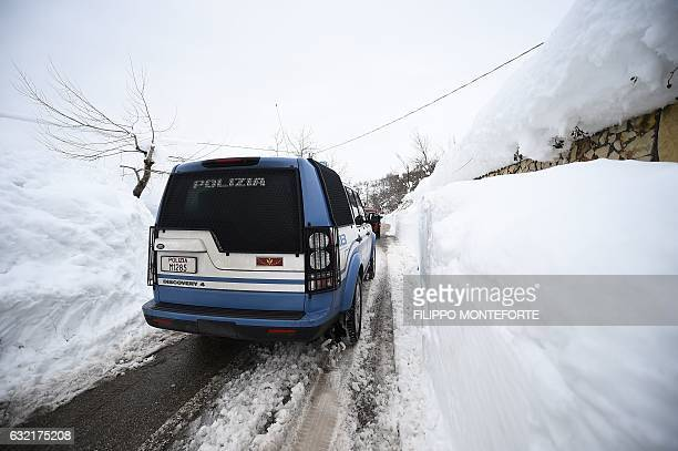 Italian police and rescuers drive through the town of Farindola as they make their way to the site of an avalanche that engulfed the Hotel Rigopiano,...