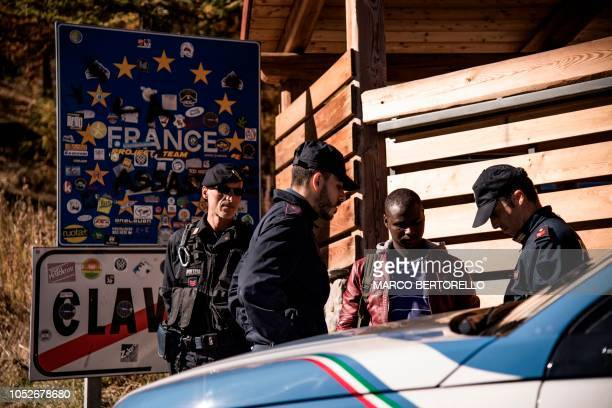 Italian Police border officers check the papers of a migrant who crossed on foot the border from France into Italy after being driven and pushed back...