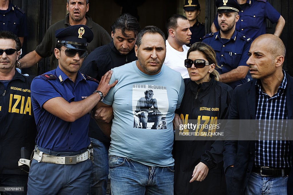 Italian Police escort camorra mafia organisation boss Cesare Pagano (C) after his arrest in Licola on July 8, 2010. Cesare Pagano is one of the 30 most wanted fugitives of Italy and is at the head of 'scissionisti' clan that was responsable of more than 80 homicides in the city of Naples and its suburbs.