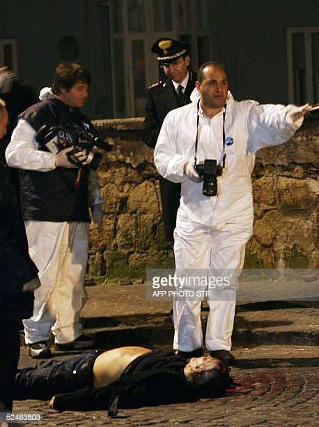 Italian police inspect the body of Nunzio Giuliano in the street after he was shot dead in Naples 21 March 2005. Giuliano was reportedly one of the...