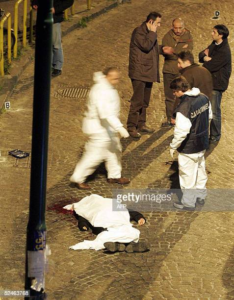 Italian police inspect the street where Nunzio Giuliano was shot in the Italian southern city of Naples 21 March 2005. Giuliano was reportedly one of...