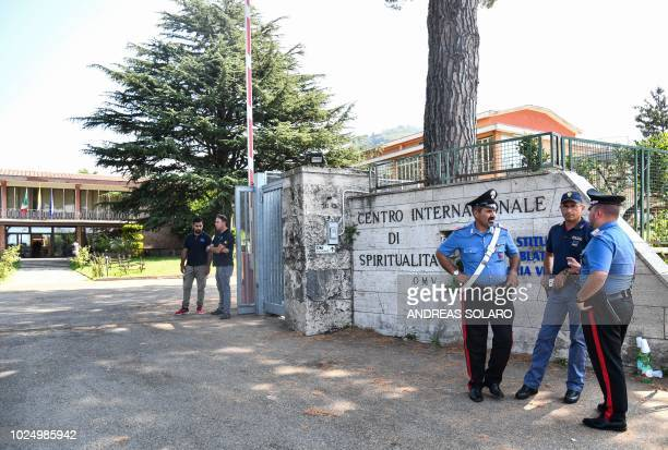 Italian police keep watch outside the Catholic Church center 'Mondo Migliore' in Rocca di Papa, near Rome, August 29, 2018. - Some 100 refugees and...