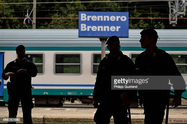 Italian police officers are silhouetted next to the station sign at the Brenner Pass on September 3 2015 in Brennero Italy Italian police have...