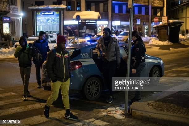 Italian Police officers escort back to Bardonecchia's train station three migrants after convincing them to give up the attempt to reach France at...