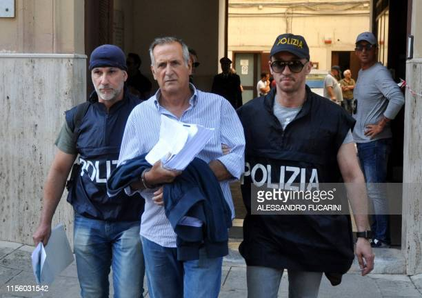 Italian police officers escort Giovanni Buscemi after he was arrested in Palermo during an police/FBI operation called 'New Connection' on July 17...