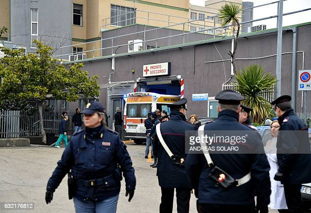 Italian police officers secure the area as an ambulance arrives at the Pescara Central hospital in the eastern coastal city of Pescara some 58...