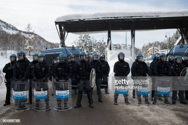 Italian police officers stand guard at the Italian border during the Briser les frontieres activist group march between Claviere Italy and...