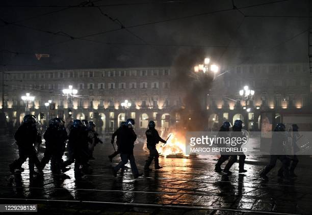 Italian police officers stand in front of a wheelie-bin on fire during a protest of far-right activists against the government restriction measures...