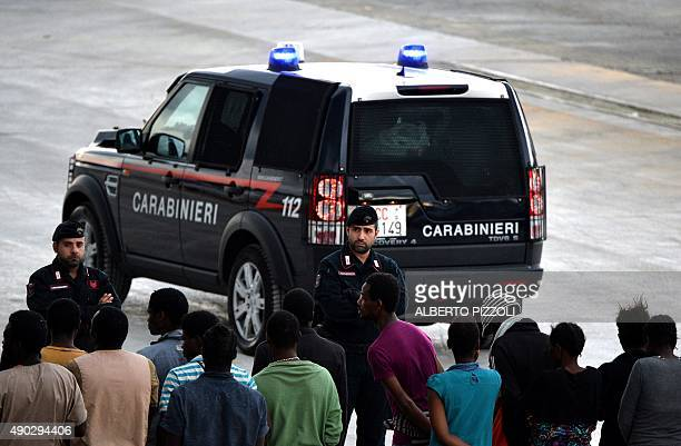 Italian police stand guard as migrants and refugees mainly from Nigeria Ghana Senegal and Sierra Leone who were transported by the German navy...