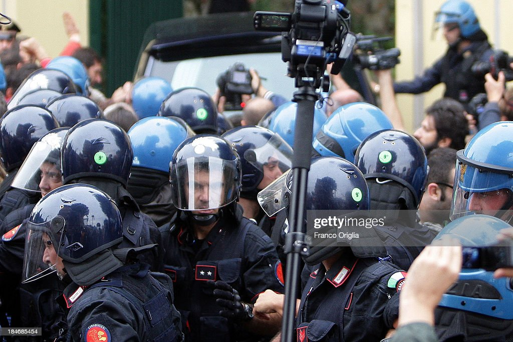 Italian Police watch as people protest as the car with the body of Erich Priebke arrives at the church of Lefebvriani on October 15, 2013 in Albano Laziale, Italy. The funeral of Erich Priebke, a former SS officer convicted of participating in the massacre of 335 citizens in Italy during World War II will now take place at the Lefebvriani Chapel in Albano Laziale, after the Catholic Church announced in a statement soon after his death that 'no public funeral would be granted to him in the city or outskirts of Rome'. His burial is not yet settled after his German hometown refused to allow his burial there.