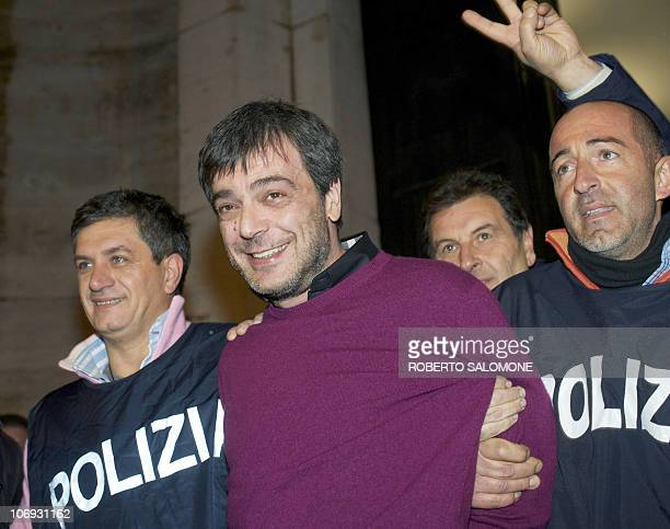 Italian policemen celebrate as they escort Antonio Iovine, one of the most powerful leaders of the Camorra organised crime group, after his arrest...