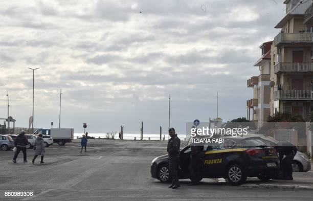 Italian policemen of the Guardia di Finanza patrol on November 28 2017 during searches in Ostia Rome's seaside district where the Spada clan lives...