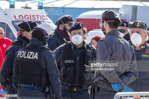 Italian policemen wearing protective masks stand on the pier in the port of Messina Sicily as migrants rescued in the Mediterranean disembark from...