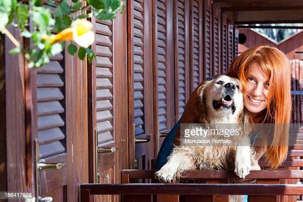 Italian politician and animalist Michela Vittoria Brambilla hugging a Golden Retriever dog in front of the bathinghuts at the lido Bau Bau Village...