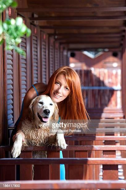 Italian politician and animalist Michela Vittoria Brambilla hugging a Golden Retriever dog in front of the bathing-huts at the lido Bau Bau Village....