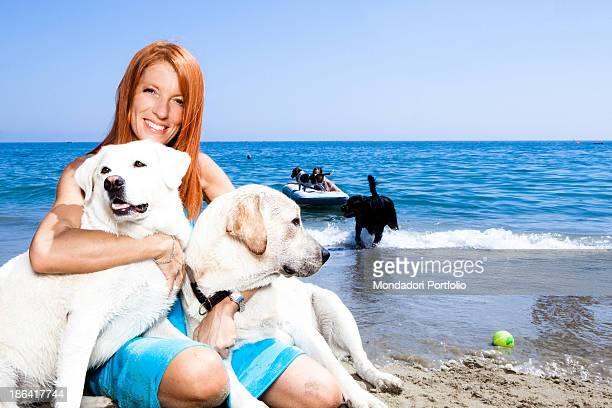 Italian politician and animalist Michela Vittoria Brambilla hugging two Labrador dogs by the sea at the lido Bau Bau Village. Albisola Marina, 22nd...