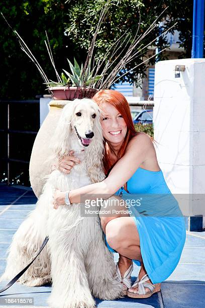 Italian politician and animalist Michela Vittoria Brambilla hugging an Afghan hound dog at the lido Bau Bau Village Albisola Marina 22nd August 2011