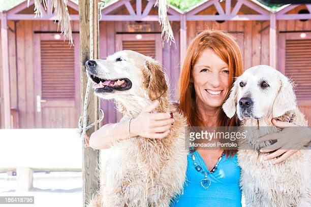 Italian politician and animalist Michela Vittoria Brambilla smiling between two Golden Retriever dogs in front of the bathinghuts at the lido Bau Bau...
