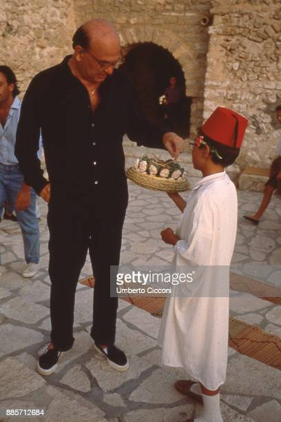 Italian Politician Bettino Craxi in Hammamet with a child who pours jasmine tea to him, 1987.