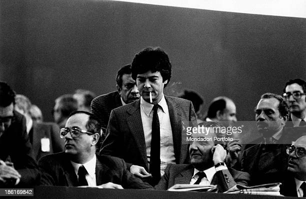 Italian politician Claudio Martelli smoking during a public meeting among other politicians including the Italian politician Rino Formica and the...
