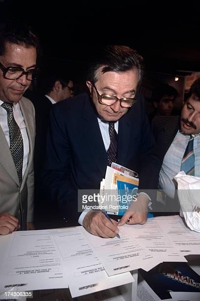 Italian politician Giulio Andreotti filling up a form Italian entrepreneur Giuseppe Ciarrapico watches the scene 1980s