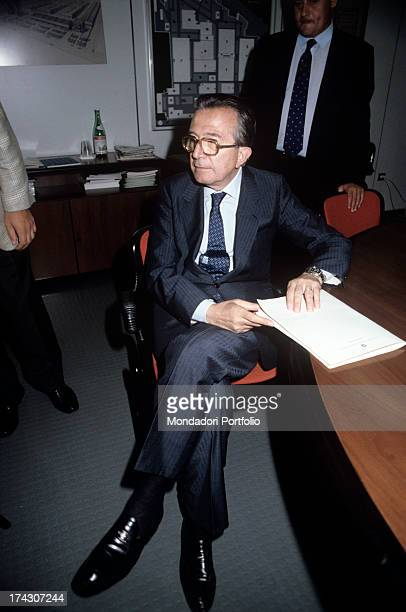 Italian politician Giulio Andreotti sitting at a table holding some documents in his hands 1980s