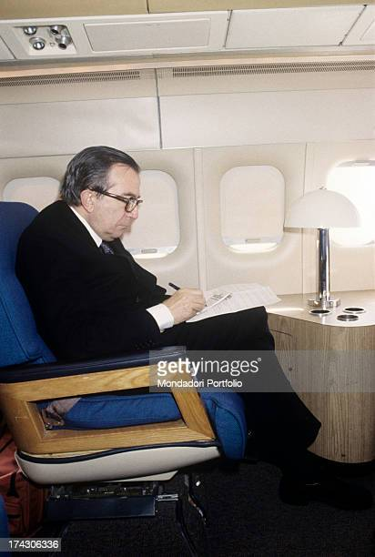 Italian politician Giulio Andreotti writing seated on the airplane 1980s