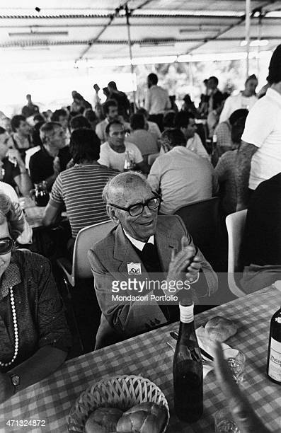 Italian politician Umberto Terracini clapping hands seated at a laid table Turin September 1981