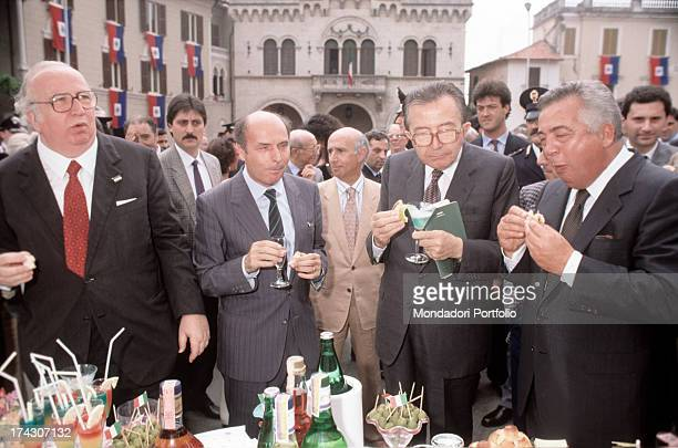 Italian politicians Giulio Andreotti and Giovanni Spadolini and Italian entrepreneur Giuseppe Ciarrapico eating and drinking during a buffet 1980s