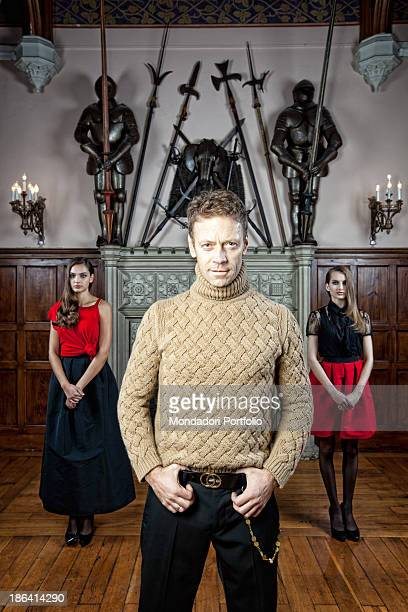 Italian pornographic actor and director Rocco Siffredi posing in the room of a villa furnished with a fireplace two suits of armour and some halberds...