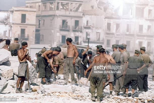 Italian POW's search for victims after a German bombing raid in Palermo Sicily Italy