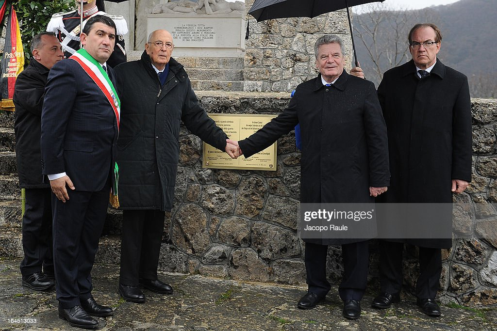 Italian President Giorgio Napolitano and his German counterpart Joachim Gauck join hands as they pay their respects to the victims of the Sant'Anna Di Stazzema Nazi Massacre on March 24, 2013 in Sant'Anna di Stazzema, near Lucca, Italy. The heads of state paid homage to the 560 victims of the Nazi massacre which took place on August 12, 1944. The ceremony was also attended by survivors and relatives of the victims.