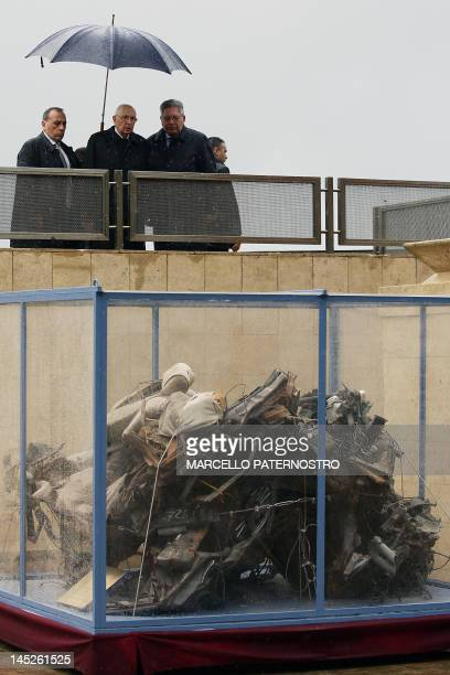 Italian President Giorgio Napolitano looks at the remains of a police car destroyed during of the assassination of top judge Giovanni Falcone during...