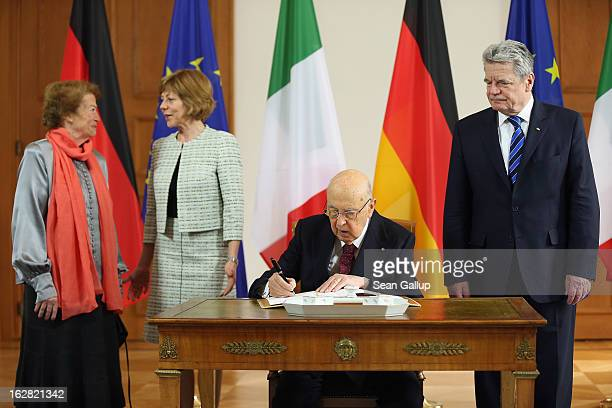 Italian President Giorgio Napolitano signs a guest book at Schloss Bellevue palace as German President Joachim Gauck, Italian First Lady Clio...
